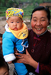 Senior woman holding child wearing colorful outfit; portrait; small village near Wuxi, China, Asia; rural China; 042403