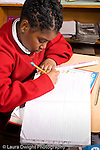 K-8 Parochial School Bronx New York Grade 3 mathematics lesson on measurement using rulers girl at work vertical