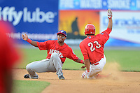 Auburn Doubledays infielder Wilmer Difo #4 attempts to tag Jiandido Tromp #23 sliding in during a game against the Williamsport Crosscutters on July 8, 2013 at Bowman Field in Williamsport, Pennsylvania.  Auburn defeated Williamsport 5-1.  (Mike Janes/Four Seam Images)