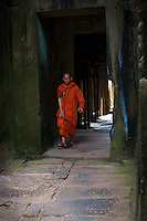 Buddhist Monk walking through the corridor at Preah Khan, Cambodia