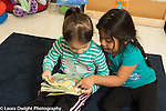 Education preschool 3 year olds two girls sitting together and looking at picture book, one girl talking and pointing to illustration