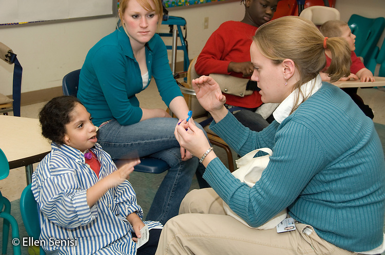 """MR / Albany, NY.Langan School at Center for Disability Services .Ungraded private school which serves individuals with multiple disabilities.Teacher holds up alphabet letters for child to identify and uses sign language (the letter """"c"""")  while teaching assistant watches. Boy: 7, African-American, Pierre Robin syndrome, limited verbal output with expressive and receptive language delays, uses sign language partially to communicate.MR: Smi24; Ris4; Hic5.© Ellen B. Senisi"""