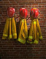 3 Firemen's coats & hard hats hanging on brick wall; orig 4x5; readiness; reliabilty, protective clothing.