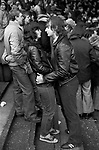 Teen couple at a Coventry City football match, not watching the game, more interested in each other. 1981, 1980s UK