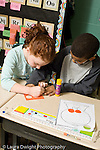 Education Elementary school Grade 2 mathematics boy and girl working together on project vertical