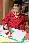 Education Preschool 3-5 year olds art activity girl painting flowers in pot vertical