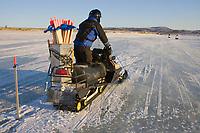 Volunteer, Steve Graham, chops hole in ice to put in wood stake trail markers on Unalakleet River near Unalakleet