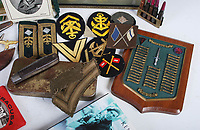 BNPS.co.uk (01202 558833)<br /> Pic: LindsayBurns/BNPS<br /> <br /> Pictured: Marine Jock Mathieson's badges.<br /> <br /> The medals, weapons and personal effects of a hero D-Day commando have sold for over £11,000 - 22 times their estimate.<br /> <br /> Marine Jock Mathieson narrowly escaped death during the Normandy landings on June 6, 1944.<br /> <br /> A bullet pierced the fuel tank of his motorbike which he was carrying above his head while wading through the sea towards Juno Beach.
