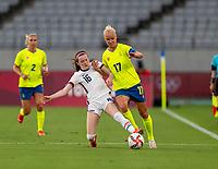 TOKYO, JAPAN - JULY 21: Rose Lavelle #16 of the USWNT tackles Caroline Seger #17 of Sweden during a game between Sweden and USWNT at Tokyo Stadium on July 21, 2021 in Tokyo, Japan.