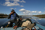 Experienced hunter and trapper Joel Peter enjoys a cigarette as he keeps watch for the Porcupine caribou to cross the Porcupine River near Old Crow, Yukon Territory, Canada..