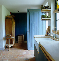 This sturdy panelled door painted a washed denim blue leads into the scullery which has a brick inlaid floor