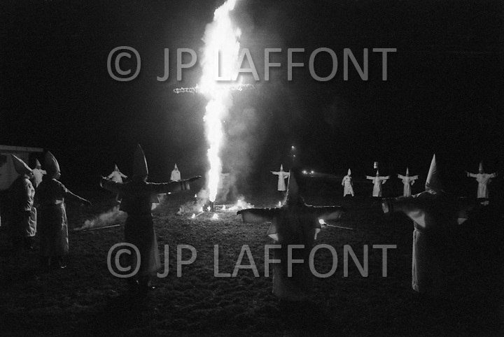 """Dunham Springs, LA. December 1976.<br /> The members of Ku Klux Klan at a night ceremony which takes place ones a month; wearing white hoods and with the cross on fire. The local group consists of 50 members; half of which are women. The leader of the cell is Bill Wilkinson who is also the leader of The National Movement, going by the title of """"Imerial Magician of the Invisible Empire of Horsemen of the KKK"""" The motto of the order is """"Be vigilant to Protect the white race."""" After the night ceremony, the members get together for dinner, preceded by a prayer."""
