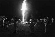 "Dunham Springs, LA. December 1976.<br /> The members of Ku Klux Klan at a night ceremony which takes place ones a month; wearing white hoods and with the cross on fire. The local group consists of 50 members; half of which are women. The leader of the cell is Bill Wilkinson who is also the leader of The National Movement, going by the title of ""Imerial Magician of the Invisible Empire of Horsemen of the KKK"" The motto of the order is ""Be vigilant to Protect the white race."" After the night ceremony, the members get together for dinner, preceded by a prayer."