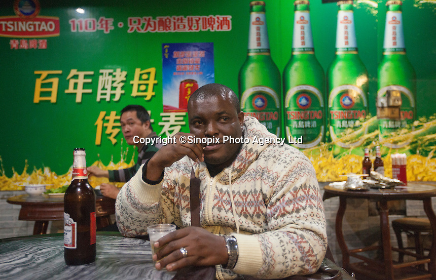 An African man enjoys a beer in a Chinese-run restaurant in an area of Guangzhou known to locals as 'Chocolate City', Guangzhou, Guangdong Province, China, 08 December 2014. The health authorities of Guangzhou are said to be stepping up their monitoring of the African community in light of the ongoing outbreak of the Ebola virus disease in West Africa.