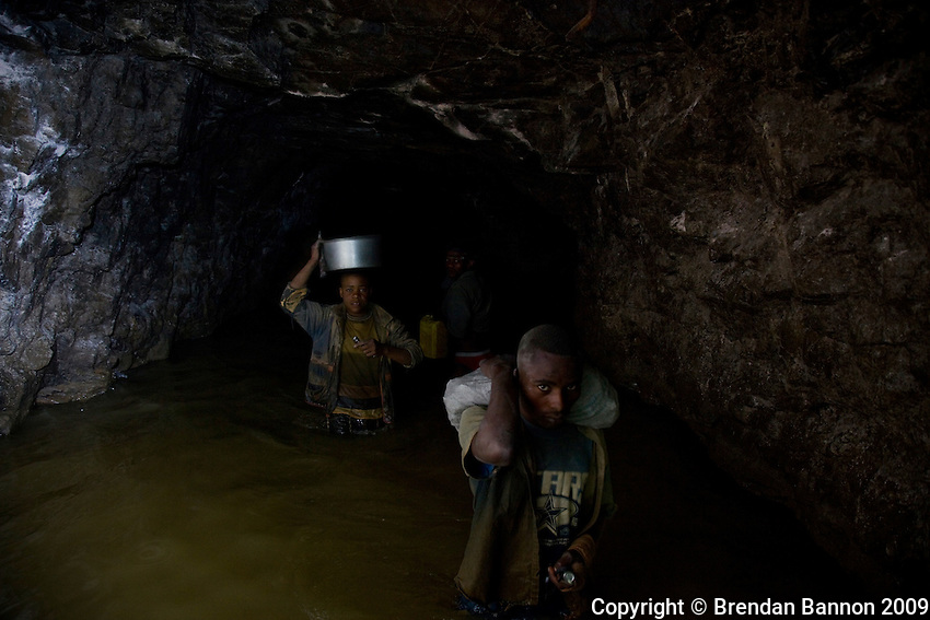 Miners emerge from the abandoned Makala mine shaft close to Mongbwalu in north eastern D.R.Congo to look for gold-bearing ore deep undrground.They are forced to walk upto 3 KM waist deep in water down disused shafts left behind by mining companies who fled during the countries civil war. Each miner will carry asack of rocks back to the surface which are then broken down in the search for flecks of gold. The mine was first opened in 1948 during Belgium's colonial reign.