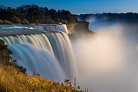 Amazing Niagara Falls long exposure view from American side, with beautiful mist and blurred water, under a blue sky at the USA and Canadian border