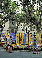 Textiles in bright Provencale colors hung on display. Golden cockerel tops stone monument. People. Uzes Provence France.