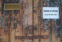 Closed wooden doors with signs on them, Bordeaux, France.