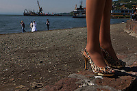 Cheap Chinese shoes are imported to Petropavlovsk. A wedding party walks along the harbor in the background.