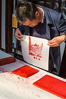 Yangzhou, Jiangsu, China.  Chinese Artist Demonstrating Block Printing Technique.