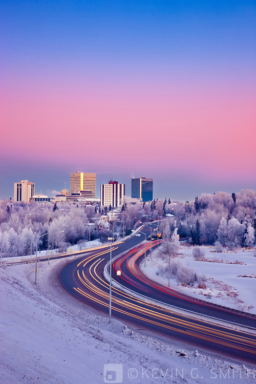 Photo of the mid winter sunset casting a pink glow on the Anchorage skyline, traffic along minnesota blvd. next to Westchester Lagoon, winter, Anchorage, Southcentral Alaska, USA.
