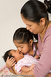 newborn baby girl one month old  Mexican American kissed by older sister age 3, held by mother vertical