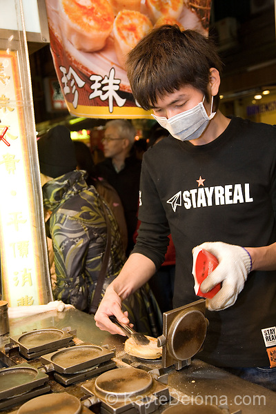 Teenager wears a facemask while making shrimp cakes at a snack bar in the seaside town of Danshui, Taipei County, Taiwan