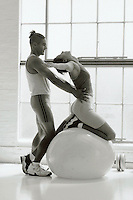 Personal training session: man assists woman with her stretching using a therapy ball.