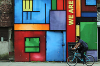 WORDS BY KARL WEST<br /> Pictured: A cyclist outside a building emblazoned with a 'We Are Here' slogan Friday 30 September 2016<br /> Re: The regeneration of the High Street in Swansea, Wales, UK