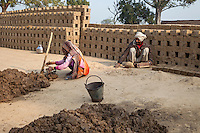 Rajasthan, India.  Wife Prepares Soft Mud while Husband Puts it into Brick Molds.