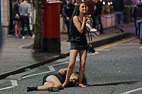 Pictured: A young woman lays on the tarmac in Swansea. Tuesday 31 December 2019 to Wednesday 01 January 2020<br /> Re: Revellers on a night out for New Year's Eve in Wind Street, Swansea, Wales, UK.