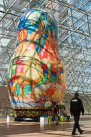Moscow, Russia, 15/06/2011..A security guard at an exhibition of of giant Russian matryoshki, or nesting dolls, in the newly-opened Afimall shopping centre. The dolls, designed by Boris Krasnov, are from 6 to 13 metres high, and each is decorated in a different style of traditional Russian folk art. This doll is in the Mstera style.