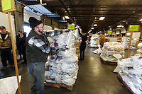 A volunteer shrink-wraps a pallet of musher's drop bags as a crew of other volunteers, including a group from the Alaska Military Youth Academy, move, weigh and stack thousands of musher food drop bags that are headed to the 22 checkpoints along the trail at the Airland Transport facility in Anchorage, Alaska on Wednesday, February 17, 2016 just prior to Iditarod 2016