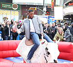 Michael Strahan rides a Mechanical Bull in Times Square