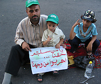 """Palestinian man and sons STAGE SIT and sat on the floor in protest at not receiving their salaries, demanding the Palestinian President Mahmoud Abbas and Prime Minister Salam Fayyad extradite paid July 12, 2007 .""""photo by Fady Adwan"""""""
