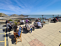 Pictured: People enjoy the sunny weather at Castellamare in Mumbles near Swansea, Wales, UK. Monday 26 April 2021<br /> Re: Lockdown rules caused by the Covid-19 Coronavirus pandemic have been relaxed, with outdoors pubs, restaurants and cafes now open in Wales, UK.