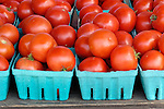 Red tomatoes in blue crate quart boxes.