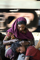 A mother picks at her child's hair for fleas as a train passes behind them on a piece of waste ground where they live beneath a flyover near Okhla station.