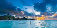 Hammock in turquoise lagoon viewing Mount Otemanu at sunset in Bora Bora, romantic honeymoon destination, near Tahiti, French Polynesia, Pacific Ocean