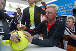 Mission Hills Vice Chairman Tenniel Chu (standing, yellow shirt) watches while tennis legend Boris Becker signs autograph after the press conference for the opening of Boris Becker Tennis Academy at Mission Hills Resort on 19 March 2016, in Shenzhen, China. Photo by Lucas Schifres / Power Sport Images