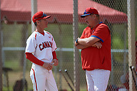 Philadelphia Phillies coach Ernie Whitt (right) talks with Greg Hamilton (left) before an exhibition game against the Canada Junior National Team on March 11, 2020 at Baseball City in St. Petersburg, Florida.  (Mike Janes/Four Seam Images)