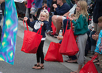 Erica Deters, 5, holds out her bag for more candy during the Bear Paw Festival Grand Parade in downtown Eagle River.