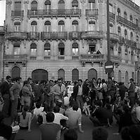 Devant le siège de l'ORTF (78 allées Jean-Jaurès). 11 ou 12 juin 1968. Vue d'ensemble groupe de manifestants : au 1er plan plusieurs étudiants sont assis par terre, au centre un manifestant vue de face tient un mégaphone (Alain Alcouffe) ; en arrière-plan, plan d'ensemble façade de l'immeuble abritant le siège de l'ORTF, quatre personnes au balcon regardent la scène. Cliché pris durant les évènements de Mai 68 à Toulouse. Observation: Alain Alcouffe est aujourd'hui professeur d'économie à l'Université de Toulouse1 (Arsenal). Cet immeuble n'existe plus aujourd'hui.