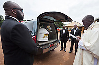 Nigeria. Enugu State. Ukana. Saint Joseph's Catholic Parish. Igbo funeral of Dr William Ikechukwu who passed away at the age of 68 years old. Before the beginning of the mass, a catholic priest blesses the white coffin in the hearse. Four strong black men, all undertakers wearing suits and bow tie, will then carry the coffin to the church. 5.07.19 © 2019 Didier Ruef