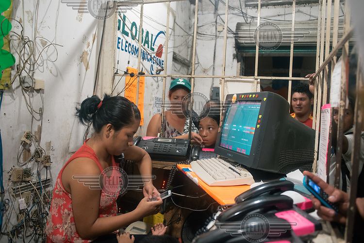 Central American migrants wait in line to speak to their relatives in a telecoms shop. The maximum amount of time they can use the phone is two minutes due to the high demand.