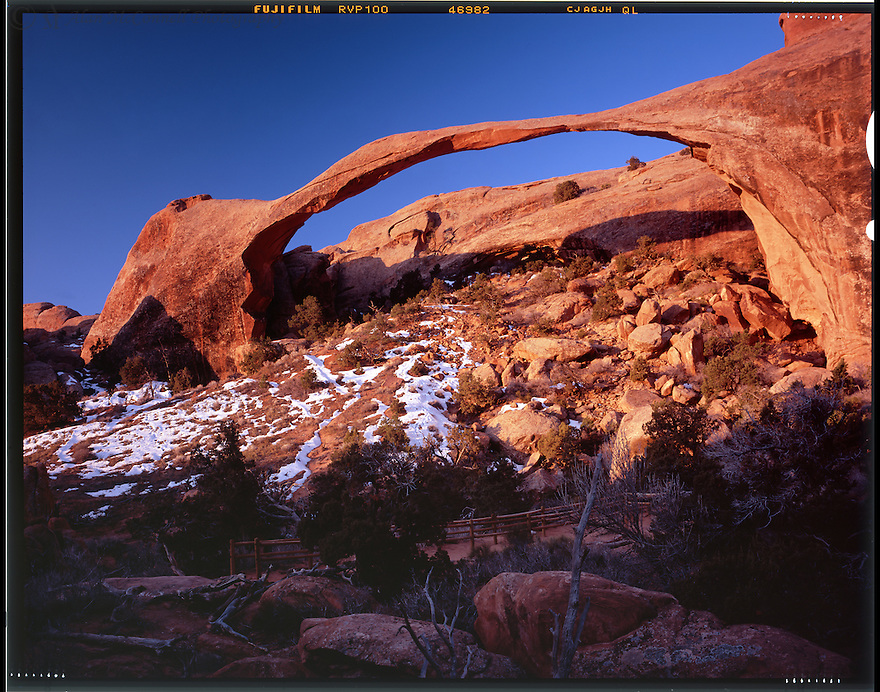 """""""Sunrise at Landscape Arch""""<br /> Arches National Park, Utah<br />  2010<br /> Naturalists at Arches National Park have cataloged more than 2,000 arches, ranging from the minimum opening of three-feet to the largest, Landscape Arch which measures 306 feet from base to base.  The most optimum time to see this marvel of nature is at sunrise.  A solitary observer can appreciate this thin span as the first warm rays of the morning sun strike the arch.  A short way down the Devils Garden Trail, you will come to the remains of Wall Arch that  succumbed to gravity in 2008.  One wonders how much longer Landscape Arch has on this relentlessly changing earth. <br /> <br /> 4 x 5 Large Format Film"""