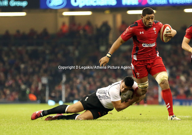 Pictured: Taulupe Faletau of Wales (with ball) is brought down by Josh Matavesi (L) of Fiji. Saturday 15 November 2014<br /> Re: Dove Men Series rugby, Wales v Fiji at the Millennium Stadium, Cardiff, south Wales, UK.