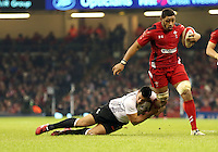 Pictured: Taulupe Faletau of Wales (with ball) is brought down by Josh Matavesi (L) of Fiji. Saturday 15 November 2014<br />