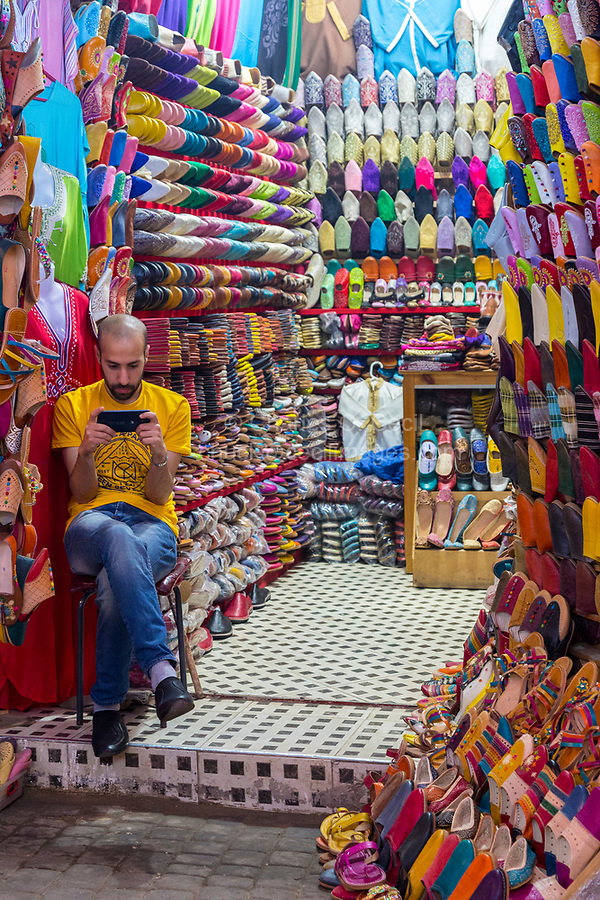 Fes, Morocco.  Vendor of Shoes and Sandals Checking his Cell Phone.  Tala'a Kabira Street Market, Fes El-Bali.