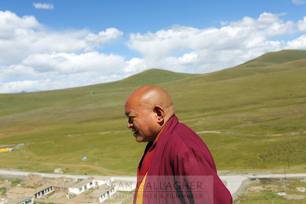 A monk on the roof of his monastery on the Tibetan Plateau, in western China.
